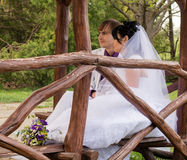 Νύφη και νεόνυμφος αγάπης ζεύγους που θέτουν τη συνεδρίαση επάνω Στοκ Εικόνα