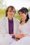 Νύφη και νεόνυμφος αγάπης ζεύγους που θέτουν τη συνεδρίαση επάνω Στοκ Φωτογραφίες
