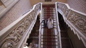 Νύφη και νεόνυμφος κάτω από τα σκαλοπάτια απόθεμα βίντεο