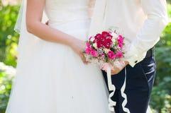 Νύφη και νεόνυμφος με μια γαμήλια ανθοδέσμη των τριαντάφυλλων Στοκ φωτογραφίες με δικαίωμα ελεύθερης χρήσης