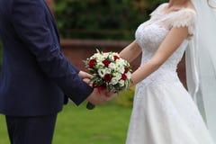 Νύφη και νεόνυμφος με την ανθοδέσμη Στοκ Φωτογραφία