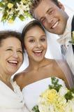 Νύφη και νεόνυμφος με τη μητέρα υπαίθρια (κινηματογράφηση σε πρώτο πλάνο) (πορτρέτο) στοκ φωτογραφία