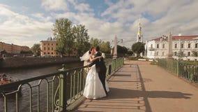 Νύφη και νεόνυμφος που αγκαλιάζουν και που φιλούν στη γέφυρα φιλμ μικρού μήκους