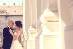 Νύφη και νεόνυμφος που αγκαλιάζουν κοντά στις στήλες Στοκ φωτογραφία με δικαίωμα ελεύθερης χρήσης