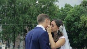 Νύφη και νεόνυμφος που αγκαλιάζουν tenderly να φιλήσει στο α φιλμ μικρού μήκους