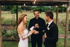Νύφη και νεόνυμφος που ανταλλάσσουν τους γαμήλιους όρκους στη γαμήλια τελετή στοκ εικόνα