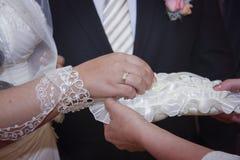Νύφη και νεόνυμφος που ανταλλάσσουν τα γαμήλια δαχτυλίδια Στοκ Εικόνες