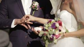 Νύφη και νεόνυμφος που ανταλλάσσουν τα γαμήλια δαχτυλίδια απόθεμα βίντεο