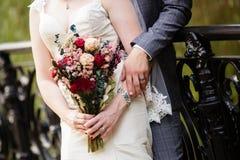 Νύφη και νεόνυμφος που επιδεικνύουν τα λουλούδια, τα δαχτυλίδια, και τα βραχιόλια τους στοκ φωτογραφίες