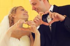 Νύφη και νεόνυμφος που κάνουν το σημάδι αγάπης με τα χέρια τους Στοκ Φωτογραφία