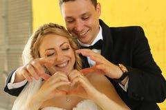 Νύφη και νεόνυμφος που κάνουν το σημάδι αγάπης με τα χέρια τους Στοκ Εικόνες