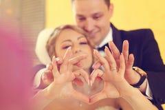 Νύφη και νεόνυμφος που κάνουν το σημάδι αγάπης με τα χέρια τους Στοκ εικόνα με δικαίωμα ελεύθερης χρήσης