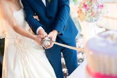 Νύφη και νεόνυμφος που κόβουν το κέικ σε μια γαμήλια τελετή Στοκ εικόνα με δικαίωμα ελεύθερης χρήσης