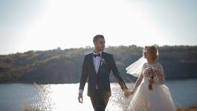 Νύφη και νεόνυμφος που περπατούν κοντά στον ποταμό απόθεμα βίντεο