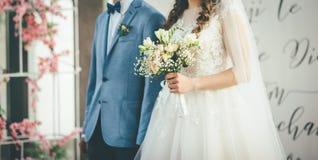 Νύφη και νεόνυμφος που περπατούν μαζί με την ανθοδέσμη στα χέρια στοκ φωτογραφίες
