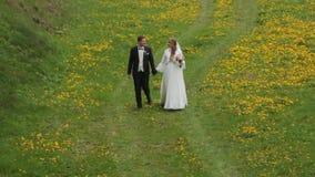 Νύφη και νεόνυμφος που περπατούν μαζί στον τομέα λουλουδιών φιλμ μικρού μήκους