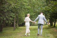 Νύφη και νεόνυμφος που περπατούν μακριά στο θερινό πάρκο υπαίθρια Στοκ εικόνα με δικαίωμα ελεύθερης χρήσης