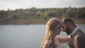 Νύφη και νεόνυμφος που περπατούν στον ποταμό, το χαμόγελο και το φίλημα απόθεμα βίντεο