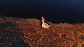 Νύφη και νεόνυμφος που περπατούν στο βουνό στην κεραία ηλιοβασιλέματος απόθεμα βίντεο