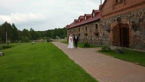 Νύφη και νεόνυμφος που περπατούν στο πάρκο του παλαιού αγροτικού σπιτιού Πυροβολισμός γερανών καμερών απόθεμα βίντεο