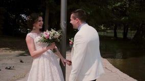 Νύφη και νεόνυμφος που στέκονται κοντά σε ένα γέλιο καρδιά-σημαδιών Το όμορφο ζεύγος απολαμβάνει τη ημέρα γάμου τους στο καλοκαίρ φιλμ μικρού μήκους