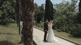 Νύφη και νεόνυμφος που στέκονται σε ένα όμορφο πάρκο φιλμ μικρού μήκους