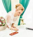 Νύφη και νεόνυμφος που υπογράφουν την άδεια γάμου ή τη γαμήλια σύμβαση Στοκ Φωτογραφία