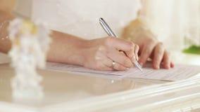 Νύφη και νεόνυμφος που υπογράφουν το πιστοποιητικό γάμου απόθεμα βίντεο