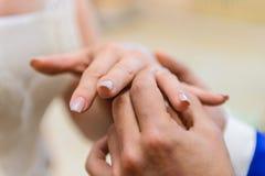 Νύφη και νεόνυμφος που φορούν τα γαμήλια δαχτυλίδια στοκ εικόνα με δικαίωμα ελεύθερης χρήσης
