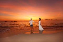 Νύφη και νεόνυμφος σε μια τροπική παραλία με το ηλιοβασίλεμα στο backg Στοκ Εικόνα