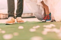 Νύφη και νεόνυμφος στα plimsolls στον πράσινο τάπητα Στοκ Φωτογραφίες