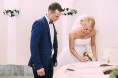 Νύφη και νεόνυμφος στην εγγραφή γάμου Ο νεόνυμφος εξετάζει στοκ φωτογραφία