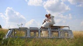 Νύφη και νεόνυμφος στην κορυφή του αναδρομικού λεωφορείου στον ηλιόλουστο θερινό τομέα Ασυνήθιστη ημέρα γάμου φιλμ μικρού μήκους