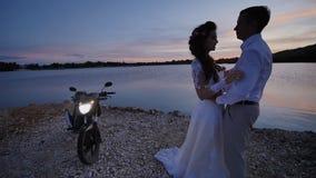 Νύφη και νεόνυμφος στην παραλία στο ηλιοβασίλεμα Θέτουν κοντά στη μοτοσικλέτα με τα φω'τα επάνω Ειδύλλιο της αγάπης απόθεμα βίντεο