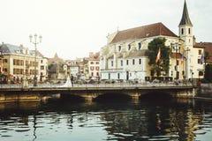 Νύφη και νεόνυμφος στην παλαιά ρομαντική γέφυρα πέρα από τον ποταμό και την εκκλησία μέσα Στοκ φωτογραφία με δικαίωμα ελεύθερης χρήσης
