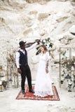 Νύφη και νεόνυμφος στο φαράγγι υπαίθρια o γαμήλια αψίδα boho Αφρικανικός άνδρας και καυκάσια γυναίκα στην ένδυση boho στοκ φωτογραφίες με δικαίωμα ελεύθερης χρήσης
