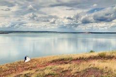 Νύφη και νεόνυμφος στο lakeshore Στοκ Εικόνες