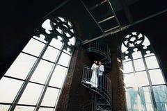 Νύφη και fiance που στέκονται στα σπειροειδή σκαλοπάτια στην παλαιά γοτθική γάτα Στοκ φωτογραφίες με δικαίωμα ελεύθερης χρήσης