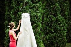 Νύφη μέσα με την τρίχα της που γίνεται σχετικά με την ένωση φορεμάτων στοκ εικόνα