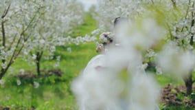 Νύφη με μια ανθοδέσμη του λουλουδιού στον κήπο απόθεμα βίντεο