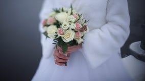 Νύφη με τα λουλούδια διαθέσιμα υπαίθρια Η νύφη είναι νευρική πριν από το γάμο Νύφη που κρατά ένα άρωμα συμπαθητικός γάμος Στοκ Φωτογραφίες