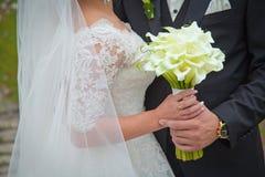 Νύφη & νεόνυμφος με τη γαμήλια ανθοδέσμη κλείστε επάνω Στοκ Φωτογραφίες