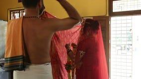 Νύφη νεόνυμφων κινηματογραφήσεων σε πρώτο πλάνο που χωρίζεται από το παραδοσιακό λεπτό κόκκινο σάλι φιλμ μικρού μήκους