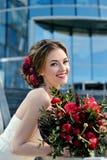 Νύφη ομορφιάς στη νυφική εσθήτα με την ανθοδέσμη στη φύση Στοκ Φωτογραφία