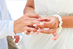 Νύφη που δίνει ένα δαχτυλίδι αρραβώνων στο νεόνυμφό της κάτω από το deco αψίδων Στοκ φωτογραφίες με δικαίωμα ελεύθερης χρήσης
