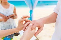 Νύφη που δίνει ένα δαχτυλίδι αρραβώνων στο νεόνυμφό της κάτω από το deco αψίδων Στοκ εικόνες με δικαίωμα ελεύθερης χρήσης