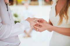 Νύφη που δίνει ένα δαχτυλίδι αρραβώνων στο νεόνυμφό της κάτω από το deco αψίδων Στοκ Εικόνες