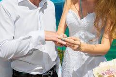 Νύφη που δίνει ένα δαχτυλίδι αρραβώνων στο νεόνυμφό του κάτω από το deco αψίδων Στοκ Φωτογραφία