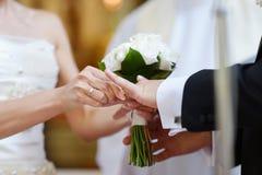 Νύφη που βάζει ένα δαχτυλίδι στο δάχτυλο του νεόνυμφου στοκ φωτογραφίες