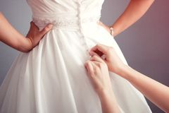 Νύφη που βάζει σε ένα γαμήλιο φόρεμα Στοκ εικόνες με δικαίωμα ελεύθερης χρήσης